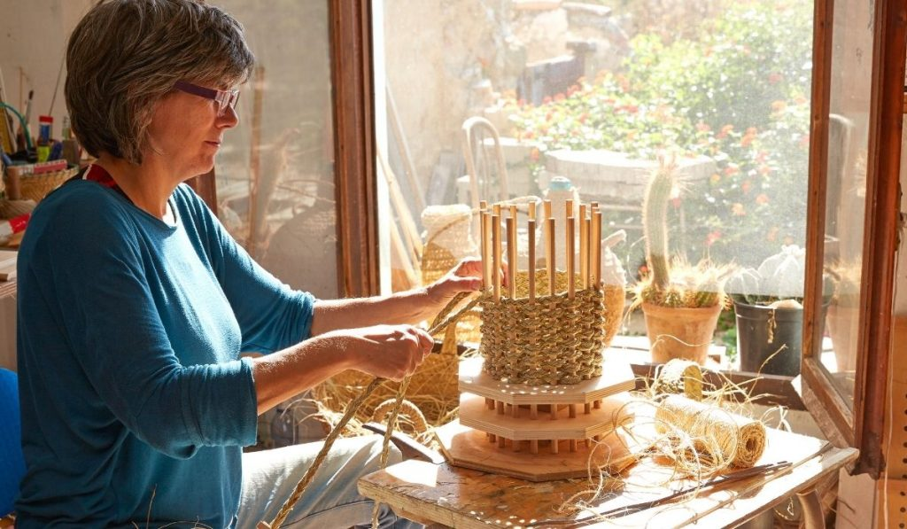 woman weaving a basket quietly at her shed