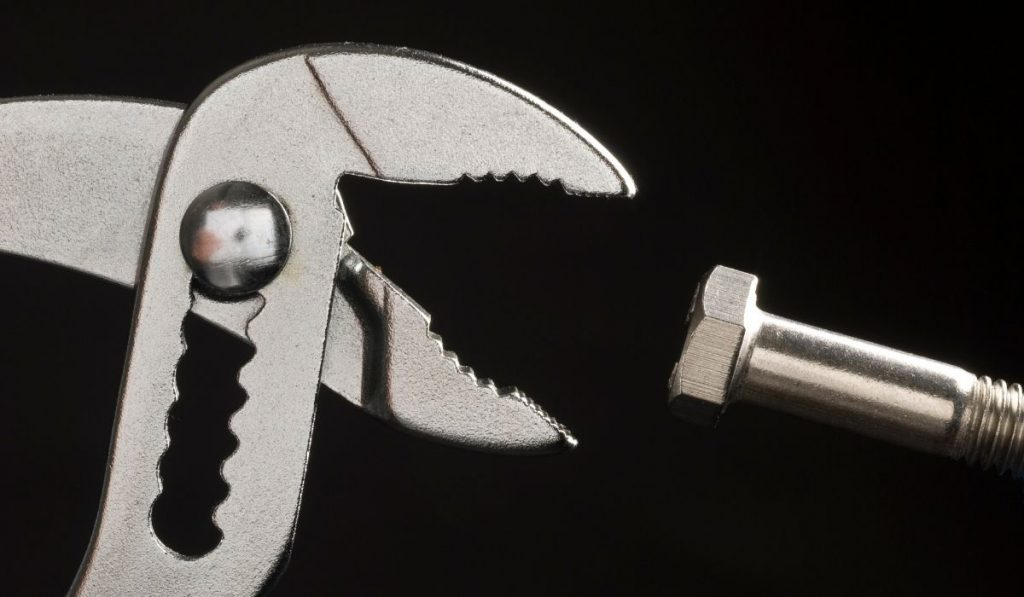 a plier and a bolt in a black background