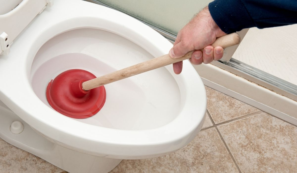 plumber unclogging toilet