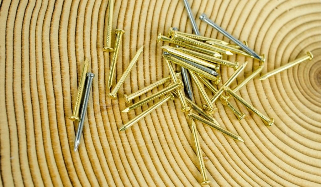 a pile of gold colored finish nails mixed in with a few silver colored brad nails on top of a gold colored mat with a concentric circle design
