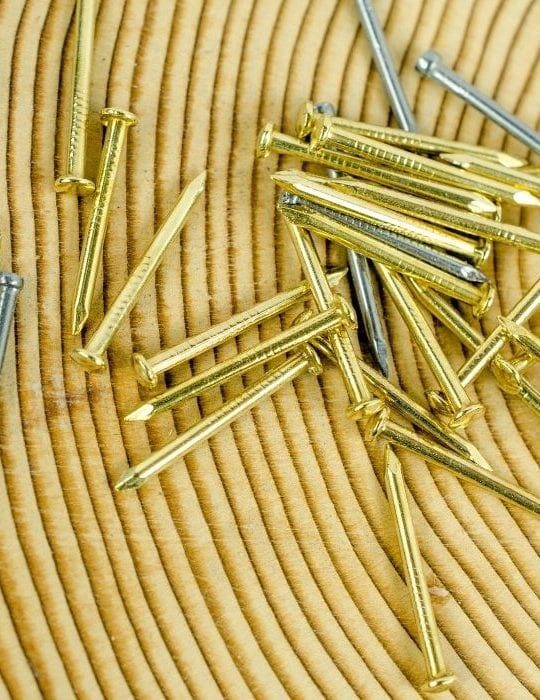 a-pile-of-gold-colored-finish-nails-mixed-in-with-a-few-silver-colored-brad-nails-on-top-of-a-gold-colored-mat-with-a-concentric-circle-design