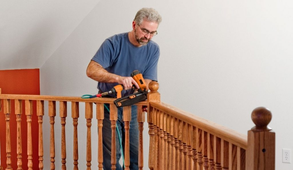 elderly man with glasses using a nailer on some wooden railings