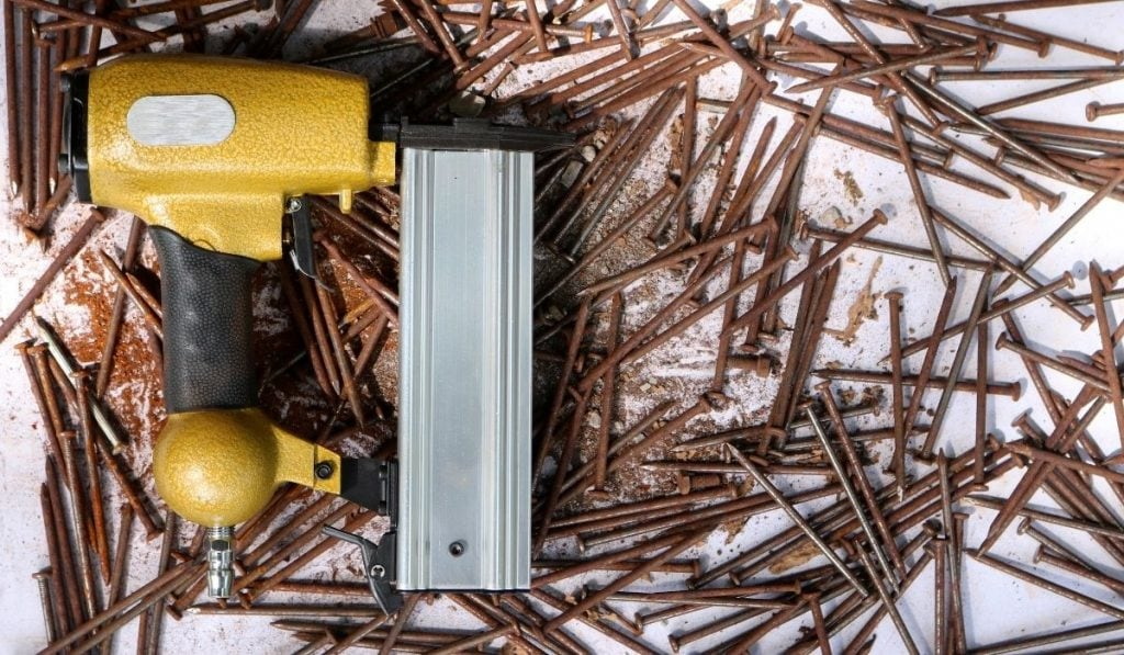 yellow-nailer-on-top-of-a-bunch-of-rusty-nails