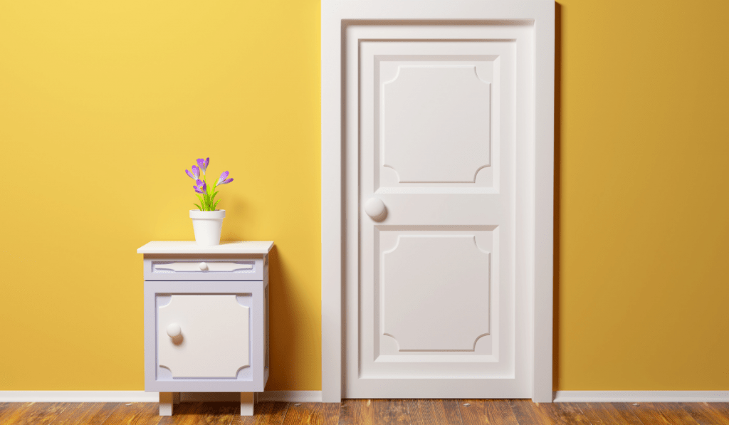 A room door  with yellow panted wall and a cabinet with lavender flower on top