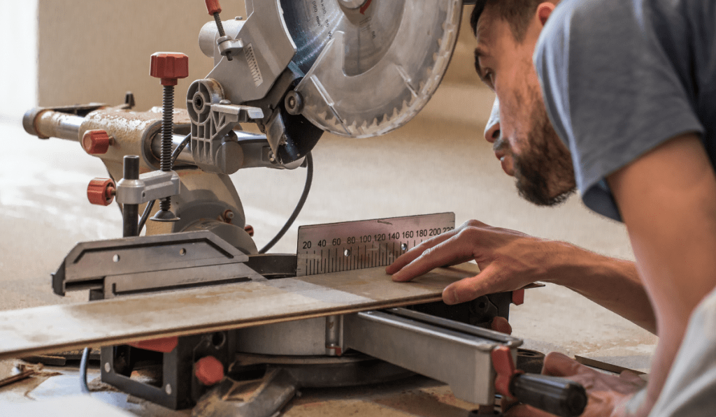 Man with a board and a miter saw