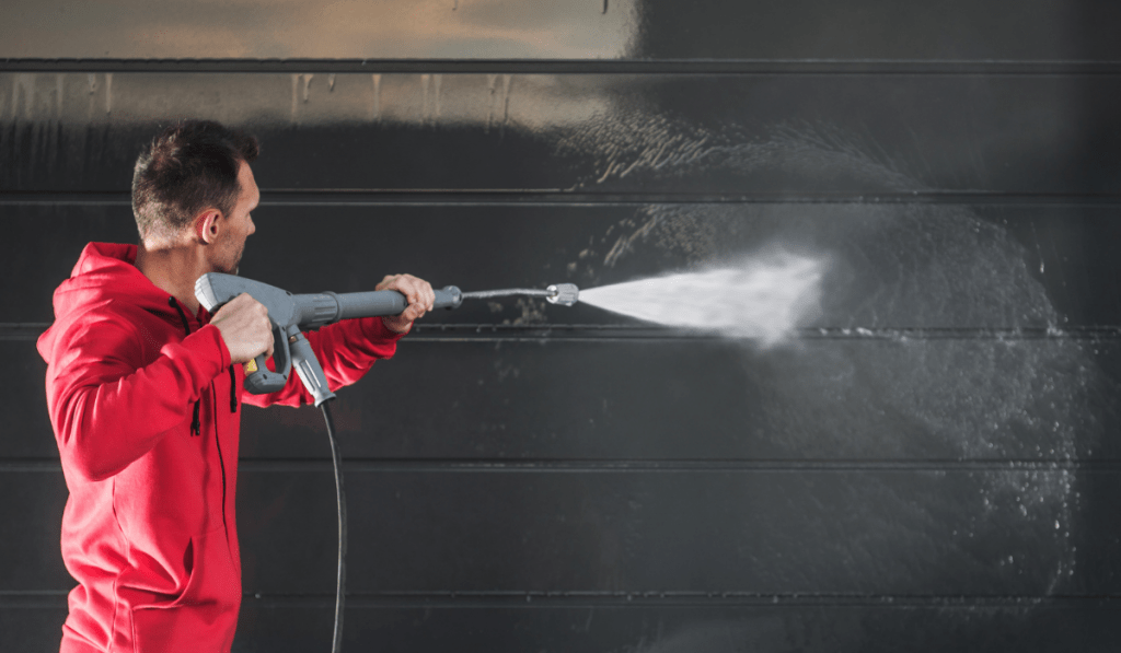 man using a pressure washer on the wall