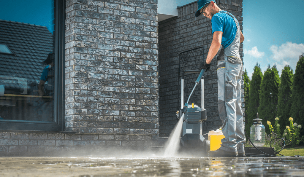 man using pressure washer in cleaning the pavement