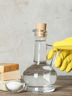 vinegar in a glass container together with some bar soaps and a scrub for cleaning