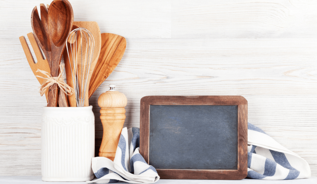Wooden kitchen utensils and a chalkboard on the side.
