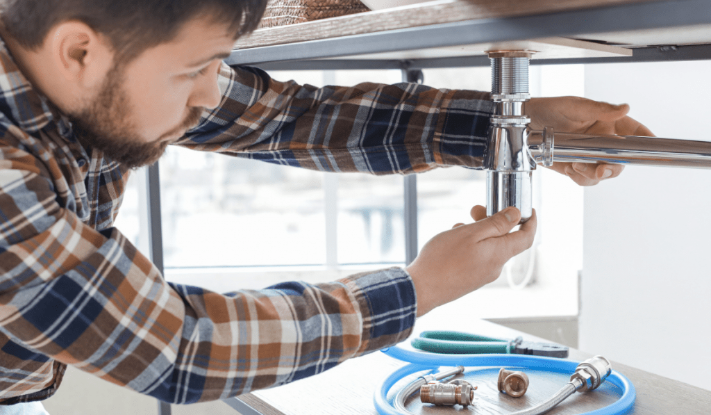 A man repairing the sink drain pipe with other parts of it below the sink.