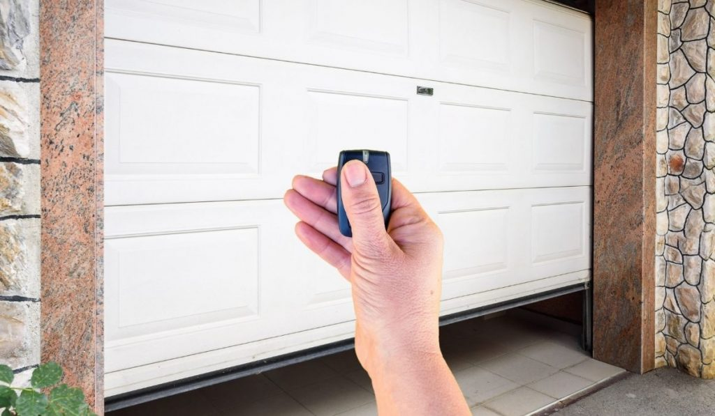 Garage Door and Hand Holding the Remote Key