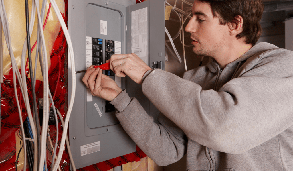 A man installing or repairing the panel with wires hanging beside the panel.