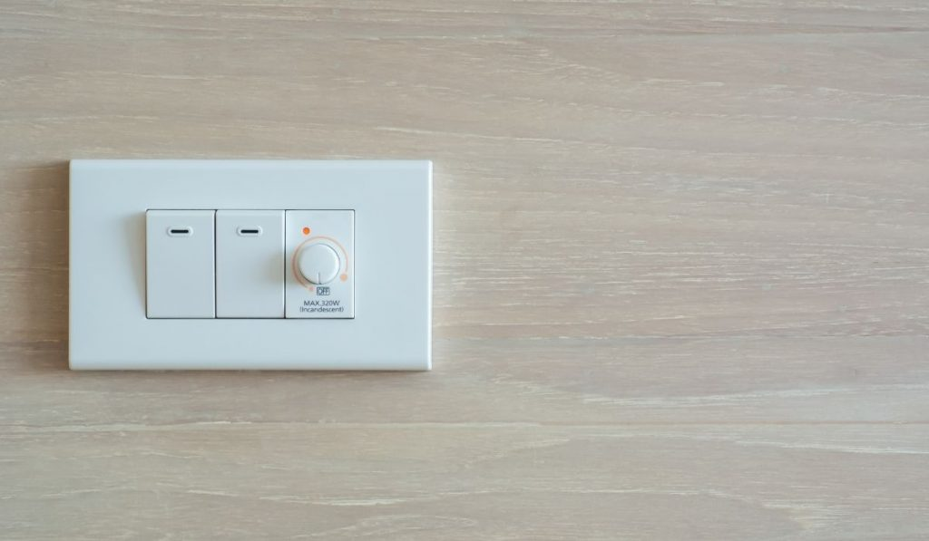 dimmer switch and light switch on a switch board