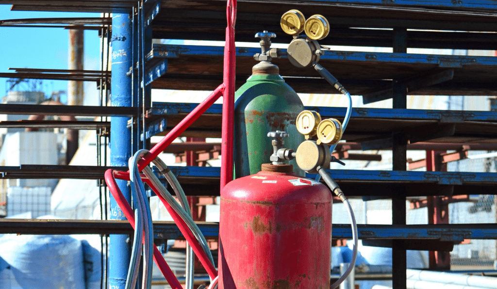 Red and green tanks waiting to be used outside the factory.