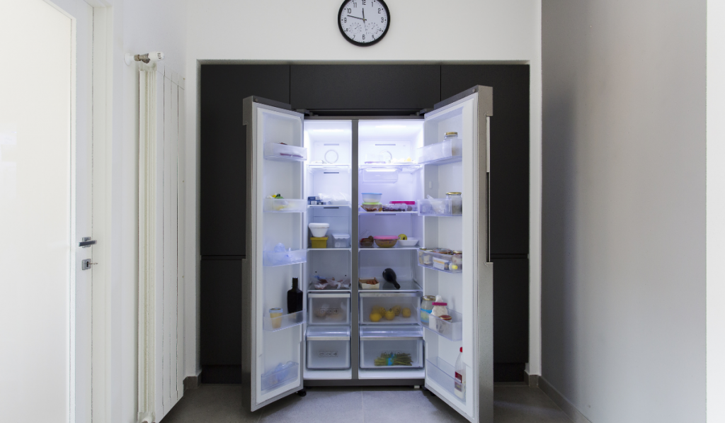 An open refrigerator at the kitchen clock above it