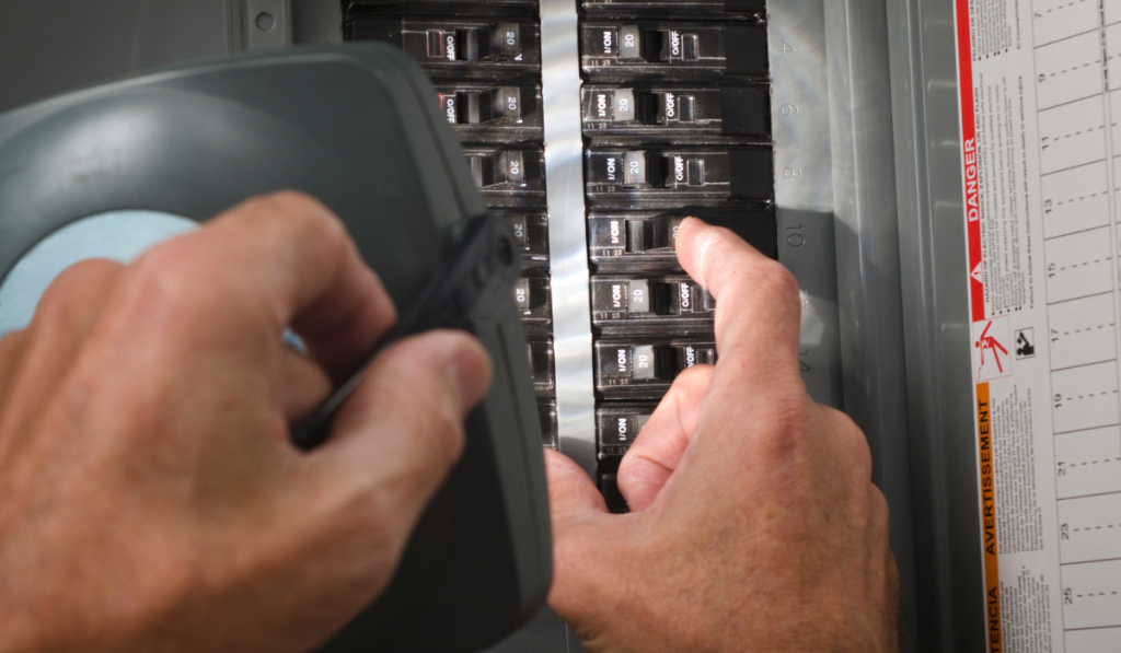 A man switching the circuit breaker while holding a spotlight