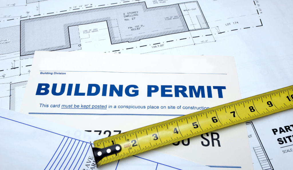 A house design with building permit application and a measuring tape.