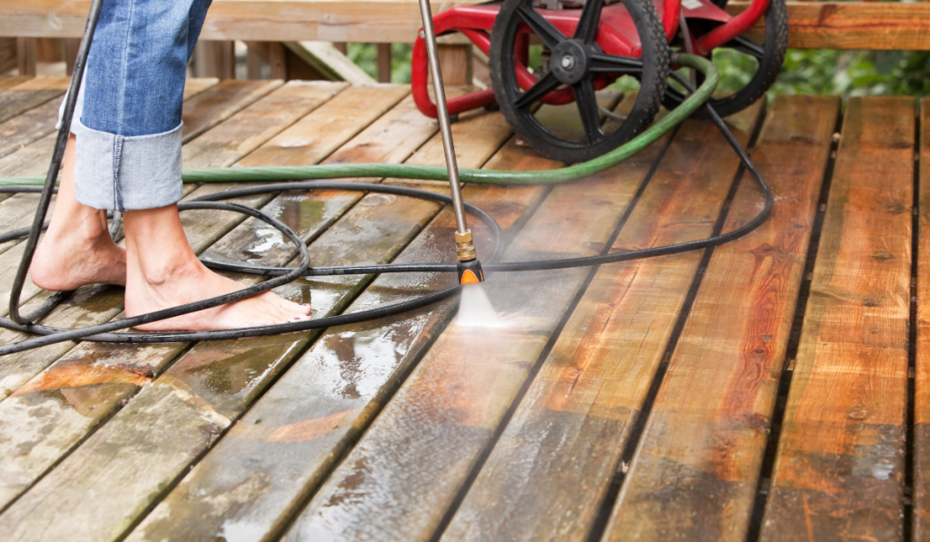 A man cleaning the deck using pressure washer