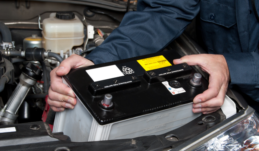 A man removing the battery in the car